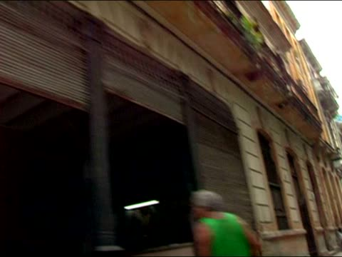 2003 medium shot car point of view shaky driving by people, parked cars and buildings on narrow streets / cuba - shaky stock videos & royalty-free footage