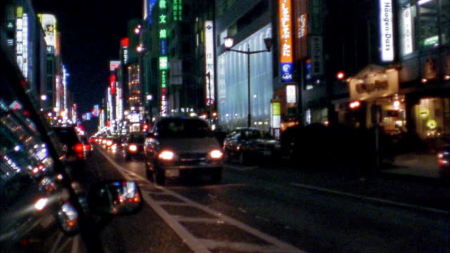 Medium shot car point of view traffic driving on street at night / Tokyo