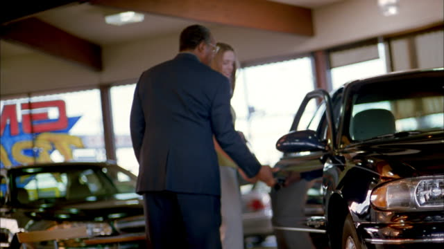 medium shot car salesman talking to female customer in salesroom and showing her car - autohandlung stock-videos und b-roll-filmmaterial