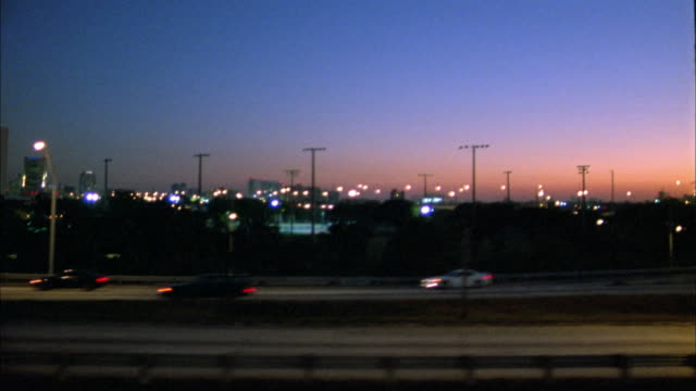 medium shot car side point of view driving on highway at dusk / miami, florida - bewegliches hintergrundbild stock-videos und b-roll-filmmaterial