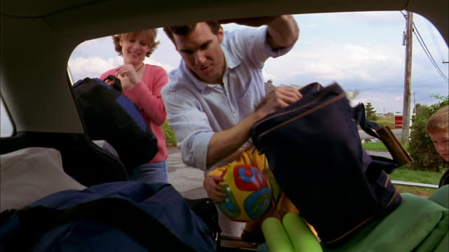 Medium shot car trunk point of view family unloading beach supplies from car