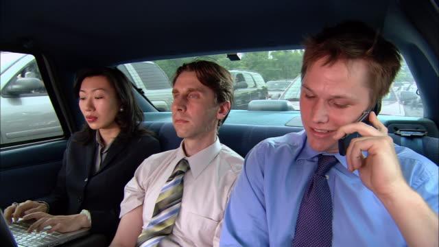 vídeos y material grabado en eventos de stock de medium shot carpool passengers in backseat /one man talking on the phone / man in the middle sneezing - estornudar