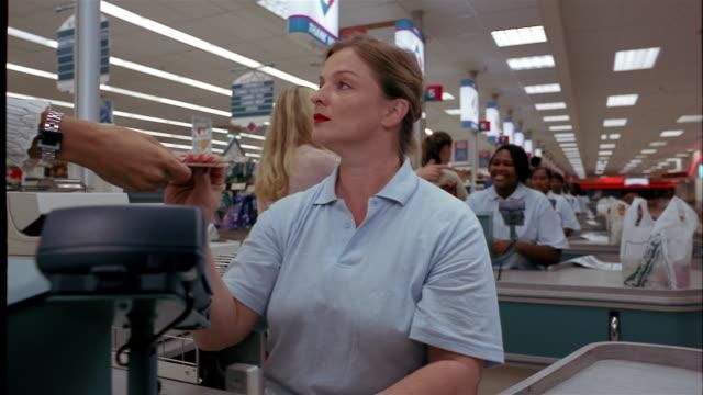 Medium shot cashier swiping Visa card at supermarket checkout