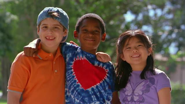medium shot caucasian boy, black boy and asian girl posing arm in arm - love emotion stock-videos und b-roll-filmmaterial