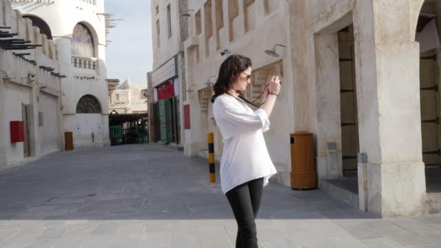 medium shot, caucasian woman walks down streets in qatar - qatar stock videos & royalty-free footage