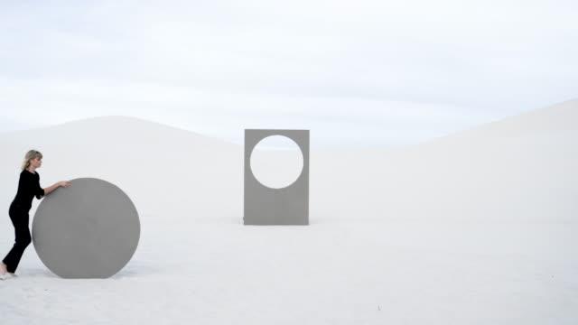 medium shot, caucasian women rolls circular portal in desert - model stock-videos und b-roll-filmmaterial