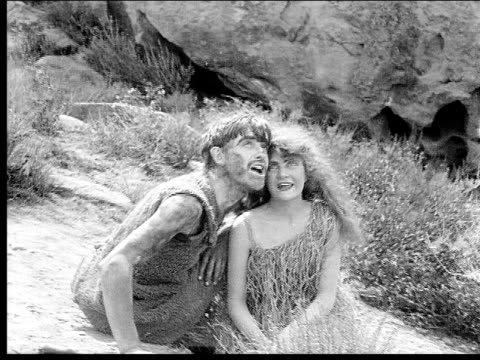 1914 B/W Medium shot Caveman and cavewoman singing on rocks