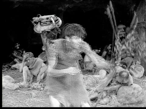 1914 B/W Medium shot Caveman inventing bow and arrow with branches, sticks and string