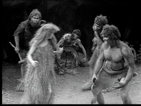 1914 B/W Medium shot Cavemen surrounding cavewoman and dragging her down by her hair