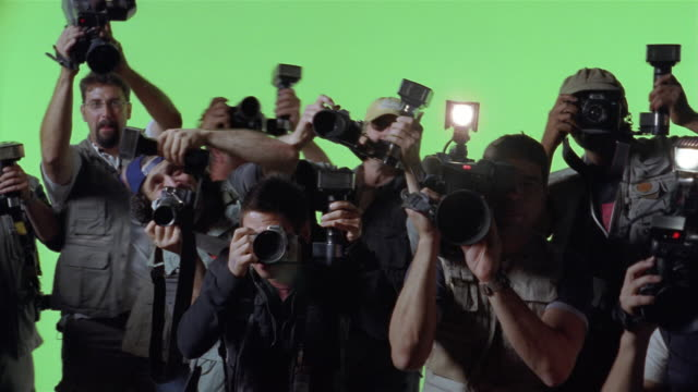 Medium shot celebrity POV of paparazzi taking photos against green screen background/ Los Angeles