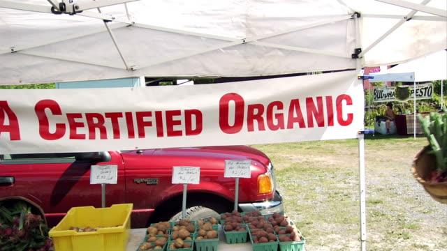 Medium shot certified organic sign at produce stand at farmers' market / man handing off bushel of beets