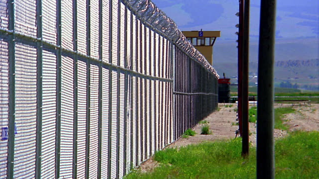 medium shot chain link fence with barbed wire at prison complex / guard tower in background - fence stock videos & royalty-free footage
