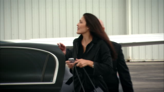 Medium shot Chauffeur opening luxury car door for businesswoman who signs documents for colleagues then enters private jet at Opa Locka Airport/ Miami, Florida, USA