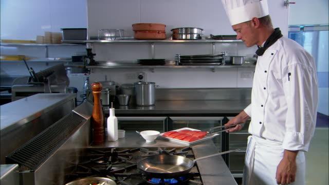 Medium shot chef cooking salmon fillet in frying pan / Auckland, New Zealand