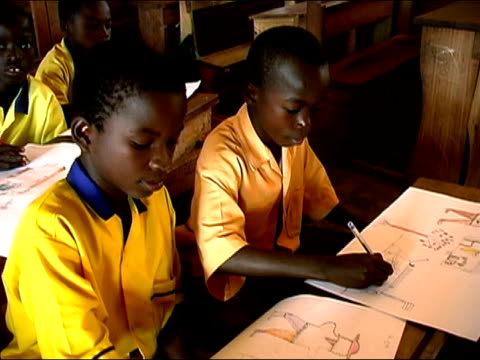 Medium shot children drawing in classroom/ zoom in close up drawings/ zoom out children at desks/ Ghana
