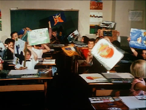 1967 medium shot children in class holding up their paintings for CAM / Russia