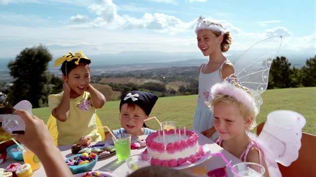 medium shot children in costumes at table with birthday cake/ boy taking photo with digital camera/ south africa - tasse oder becher stock-videos und b-roll-filmmaterial