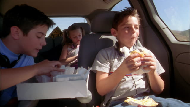 Medium shot children in minivan eating fast food hamburgers and french fries