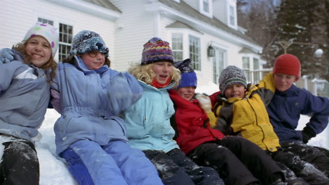 Medium shot children in winter clothing sitting in a row and smiling at CAM/ putting arms around each other/ VT