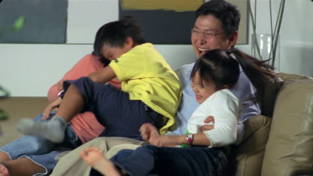 Medium shot children jumping on sofa falling into arms of father / children and father hugging