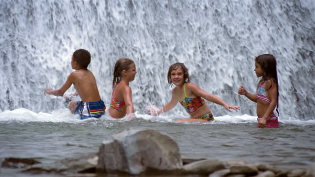 Medium shot children playing in water at foot of waterfalls / Stony Brook State Park, New York