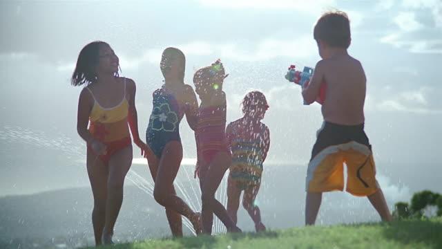medium shot children running through sprinkler in their swimsuits / boy shooting water gun / south africa - squirt gun stock videos and b-roll footage
