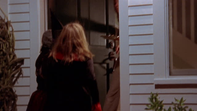 medium shot children running up to doorstep in halloween costumes / woman opening door and handing out treats - vampire stock videos and b-roll footage
