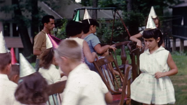 1960 medium shot children wearing party hats playing musical chairs in backyard / swingset in background
