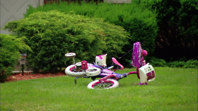 medium shot child's bike lying overturned on lawn - abandoned stock videos & royalty-free footage