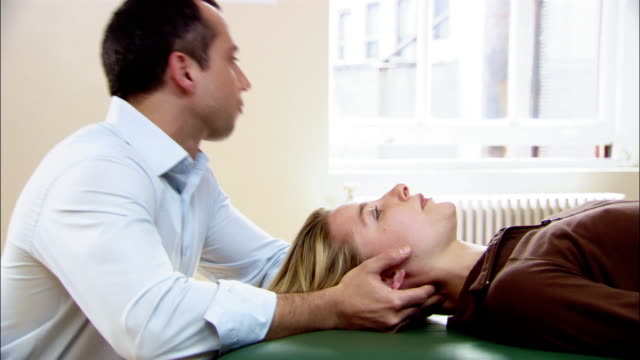 Medium shot chiropractor adjusting woman's neck as she lies on table