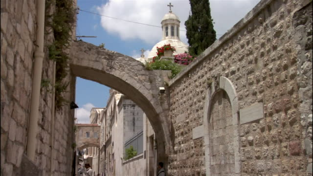 medium shot church dome zoom out man walking down via dolorosa/ jerusalem - ヴィアドロローサ点の映像素材/bロール