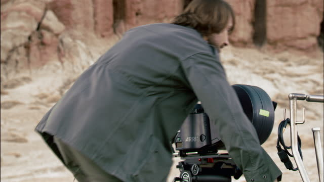 Medium shot cinematographer walking around film camera / looking through camera and moving it back and forth / Red Rock Canyon State Park, California