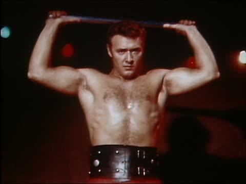 1961 medium shot circus strongman bending metal bar around his neck - inarcare la schiena video stock e b–roll