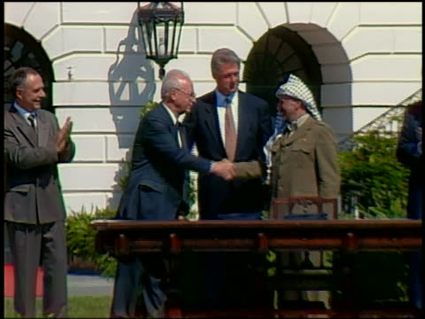 1993 medium shot clinton standing behind arafat and rabin shaking hands washington dc - frieden stock-videos und b-roll-filmmaterial