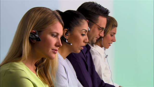 vídeos y material grabado en eventos de stock de medium shot - close-up four customer service representatives wearing hands-free devices side by side - call center latino