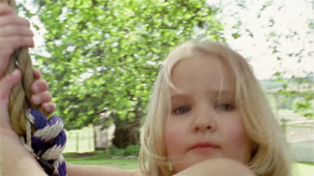 medium shot - close-up girl swinging on tire swing near house / des moines, king county, washington, usa - tire swing stock videos & royalty-free footage