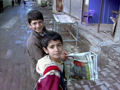 medium shot closeup two boys reading crossword puzzle in newspaper and smiling/ turkey - crossword stock videos and b-roll footage