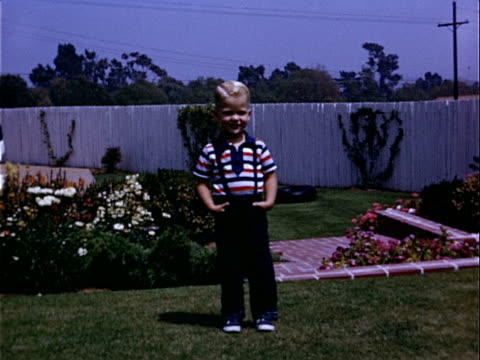 1952 Medium shot - close-up Young boy standing in flower garden with hands in his pockets and walking toward camera / Beverly Hills, California, USA