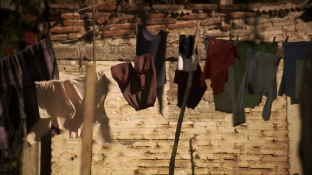 vidéos et rushes de medium shot clothes hanging out to dry on clothesline blowing in wind - dry clothes