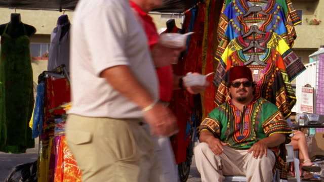 vídeos y material grabado en eventos de stock de medium shot clothing vendor sitting in market tent with people passing in foreground / venice beach, ca - kelly mason videos