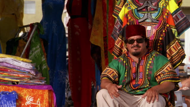 vídeos y material grabado en eventos de stock de medium shot clothing vendor wearing sunglasses and fez sitting in market stall / venice beach, ca - kelly mason videos
