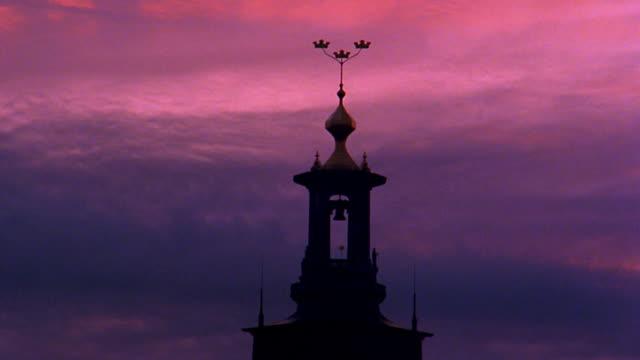 vidéos et rushes de medium shot clouds rolling behind spire of stockholm cathedral at dusk / sweden - flèche clocher