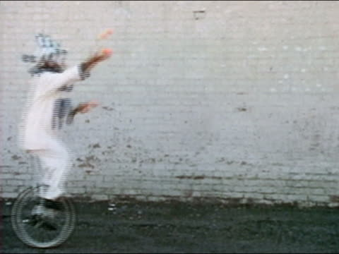 1969 medium shot clown riding unicycle and juggling / AUDIO