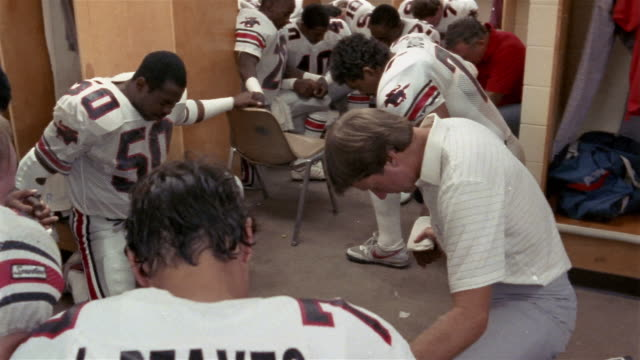 1985 Medium shot Coach Steve Spurrier and Tampa Bay Bandits football players praying in locker room before game / USA