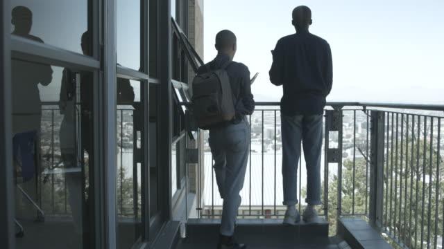 medium shot, college students have discussion on library balcony - spegling bildbanksvideor och videomaterial från bakom kulisserna