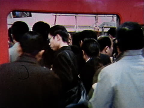 1970 medium shot commuters crowding onto subway train at rush hour / zoom in man wearing mask to prevent spread of illness / japan - showa period stock videos & royalty-free footage