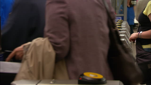 medium shot commuters passing through turnstiles with oyster card readers at westminster tube station / london - turnstile stock videos & royalty-free footage