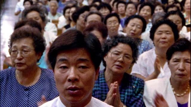 medium shot congregation church singing and clapping hands / south korea - singen stock-videos und b-roll-filmmaterial