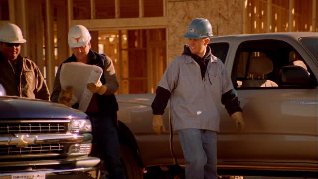 medium shot construction workers looking at blueprints on hood of truck / phoenix, arizona - 45 49 år bildbanksvideor och videomaterial från bakom kulisserna