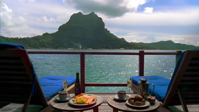 Medium shot continental breakfast laid out between lounge chairs with Mount Otemanu in background / Bora Bora